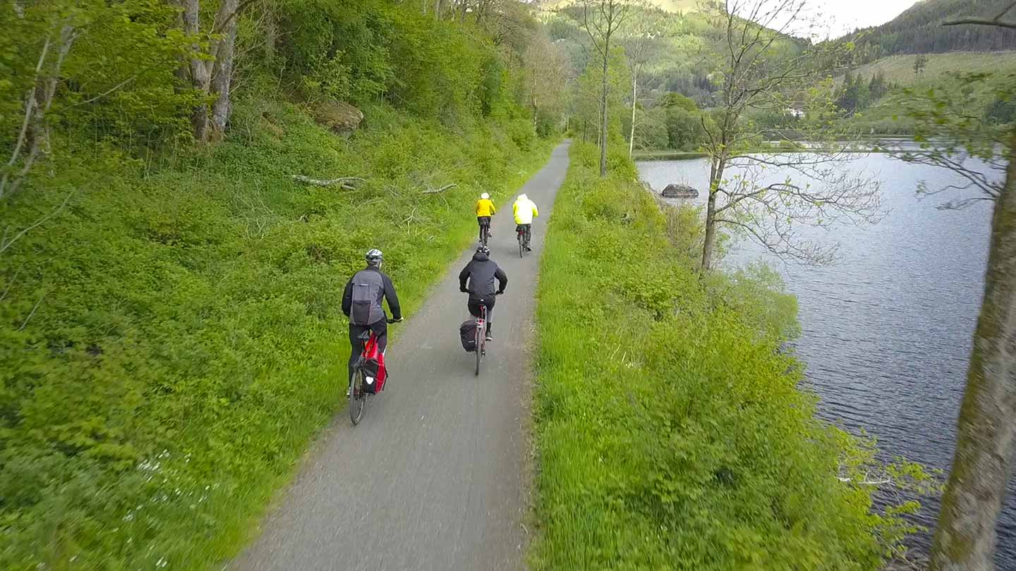Four riders travelling along a traffic free cycle track with wooded hillside on left and loch on right.