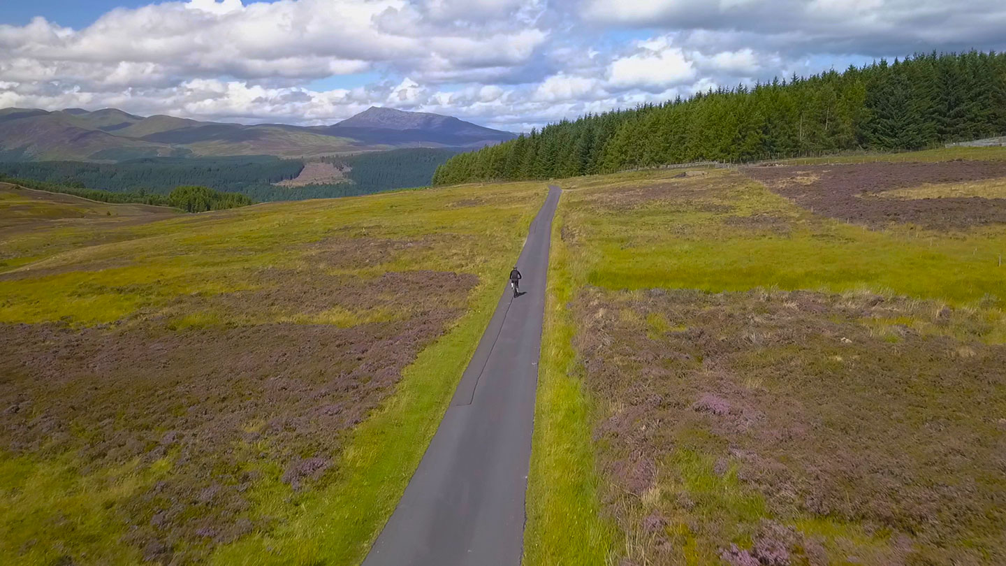 Cyclist riding along road bordered by purple blooming heather with Schehallion in the background