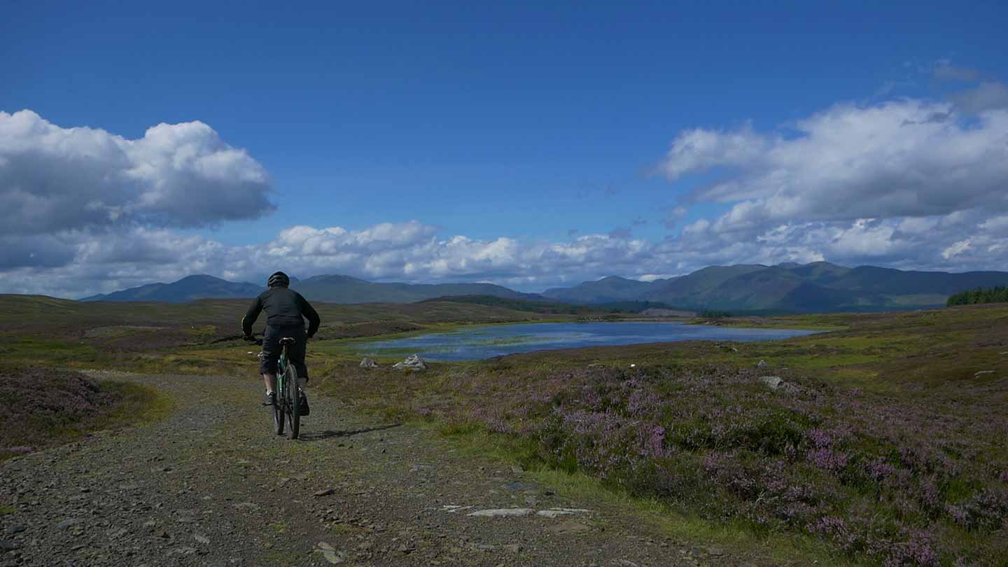 A cyclist in the foreground riding along a rough track with loch in the middle ground and high mountains of Scotland's Central Highlands in the background