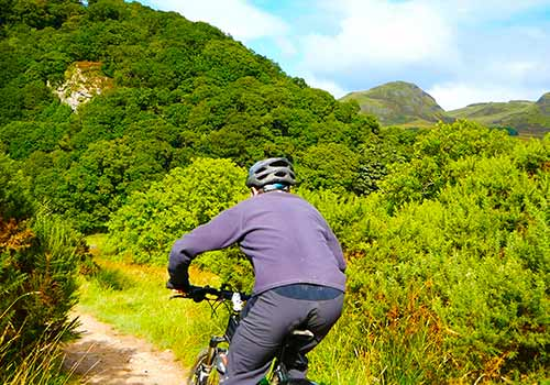 Trail cyclist blasting through rural Stirlingshire with the volcanic plug Duntruin in the background