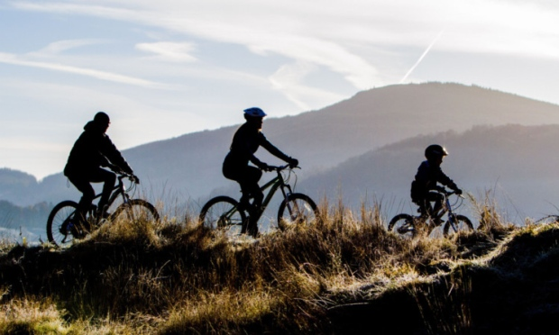 A family of three cycling in the Scottish hills
